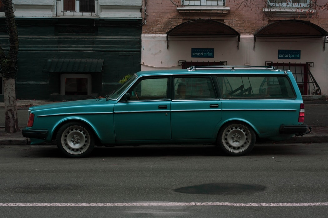 An older Volvo estate vehicle parked in front of a store