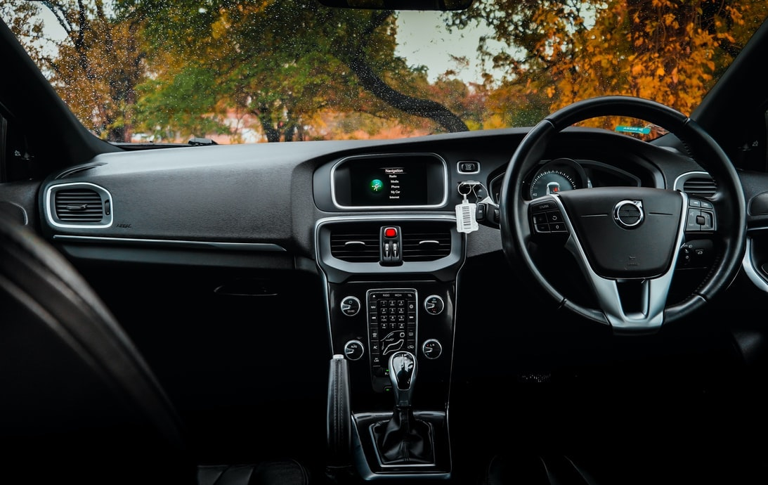 An interior dashboard of a modern Volvo viewed from the back seat